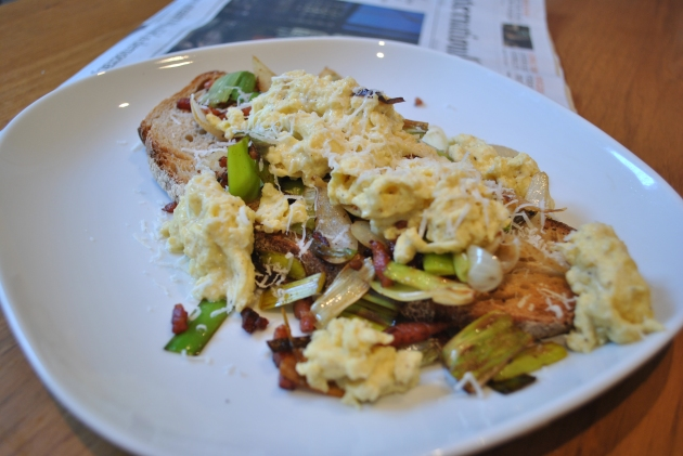 Scrambled eggs on toast with fried leek, pancetta and onion